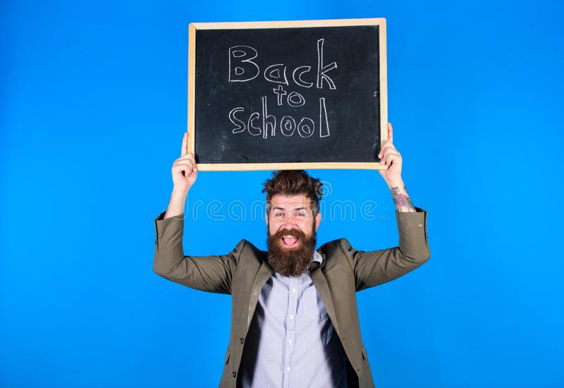 El hombre barbudo del profesor sostiene la pizarra con la inscripci?n de nuevo a fondo del azul de la escuela Empleo agotador de  fotografía de archivo