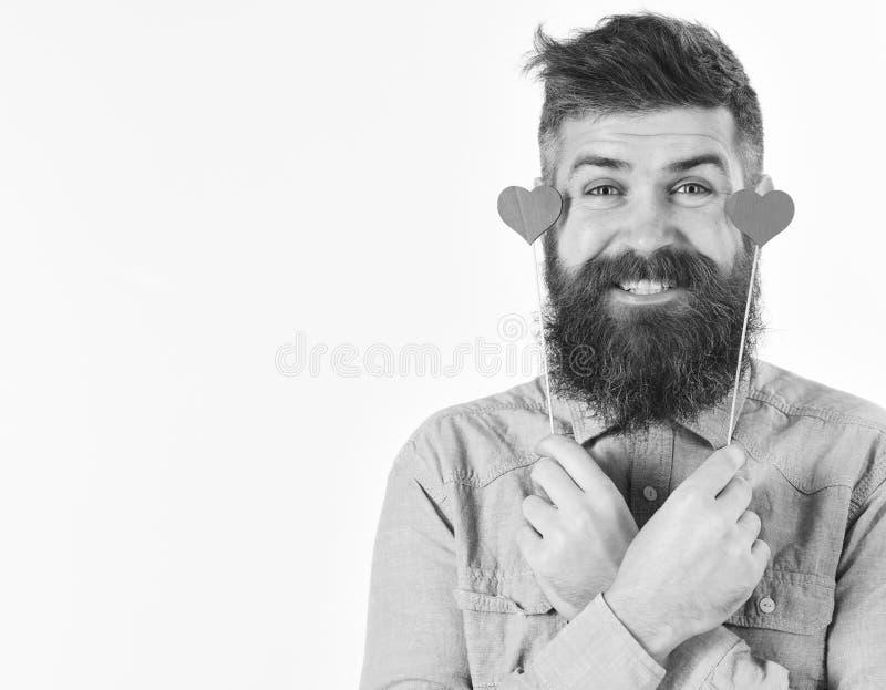 El hombre barbudo detiene a pequeñas tarjetas del día de San Valentín de los corazones fotos de archivo