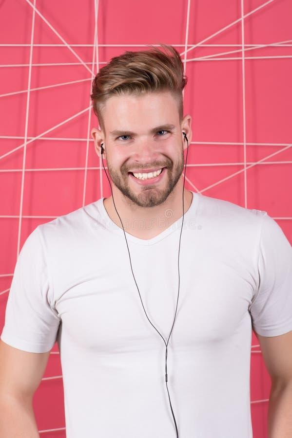 El hombre barbudo disfruta de música que escucha con los auriculares Machista feliz con el dispositivo audio del auricular Medios foto de archivo libre de regalías