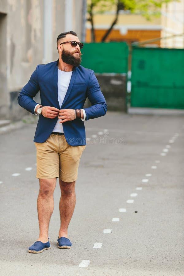 El hombre barbudo elegante camina a través de la ciudad foto de archivo