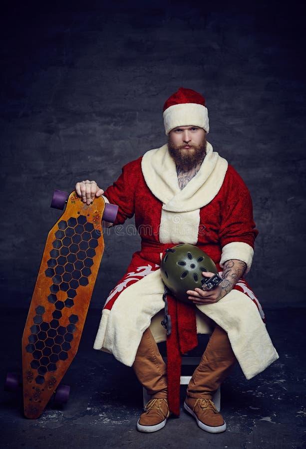 El hombre barbudo en el ` s de Papá Noel viste llevar a cabo al tablero largo foto de archivo libre de regalías