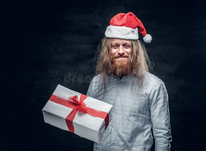 El hombre barbudo en sombrero del ` s de Papá Noel sostiene la actual caja foto de archivo libre de regalías