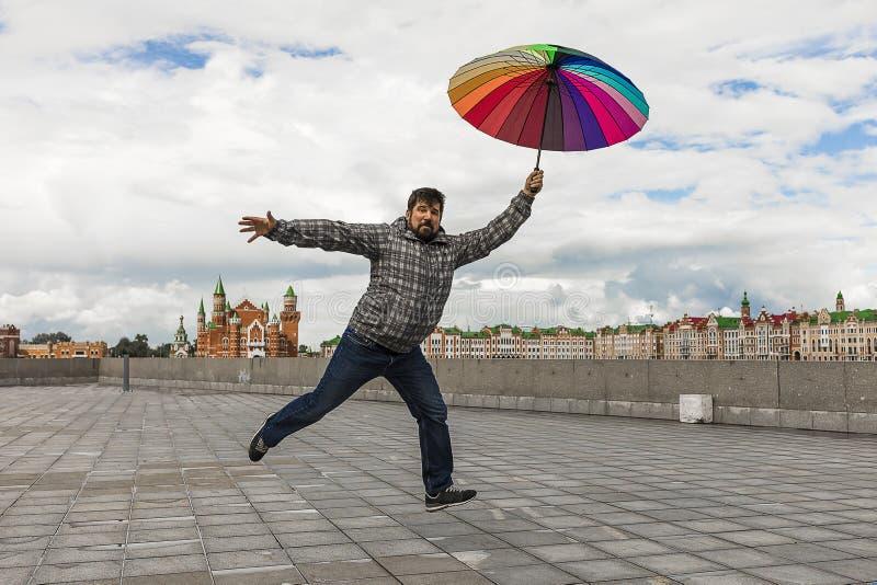 el hombre barbudo en el terraplén que salta como un niño con el paraguas coloreado fotos de archivo libres de regalías