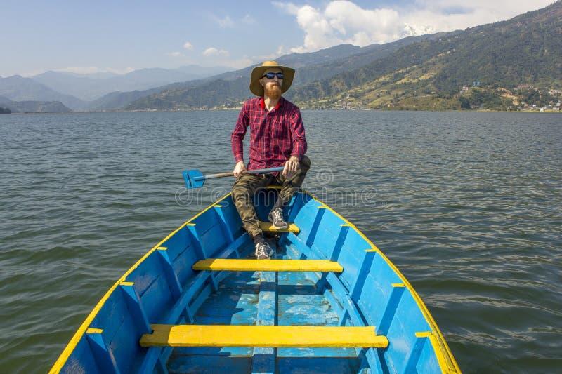 El hombre barbudo en una camisa, un sombrero y gafas de sol rojos se sienta en un barco de madera azul con una paleta en el lago  fotografía de archivo