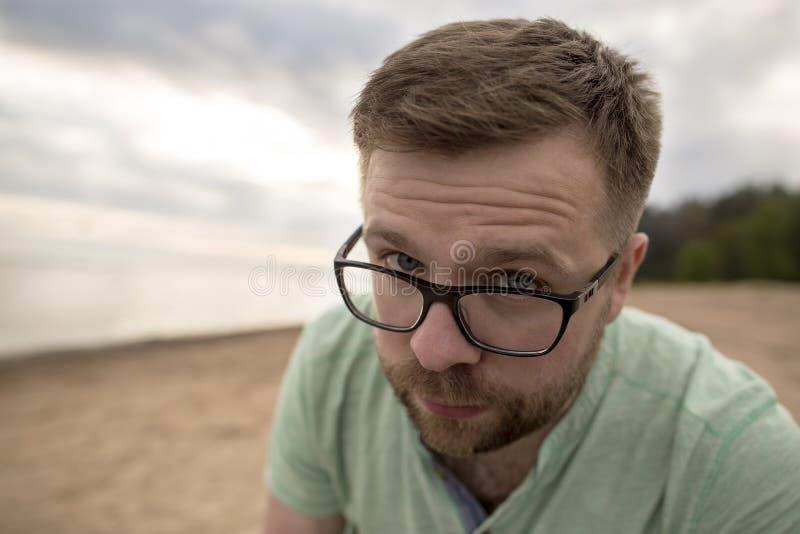 El hombre barbudo en vidrios mira questioningly ojos azules que frunce el ceño, o foto de archivo