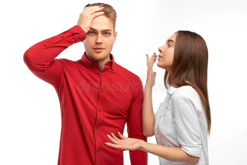 El hombre barbudo enojado puso su mano en su frente, gritos de la mujer con emociones negativas en colega imagen de archivo libre de regalías