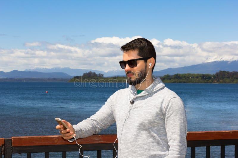 El hombre barbudo está utilizando el teléfono móvil fotografía de archivo libre de regalías