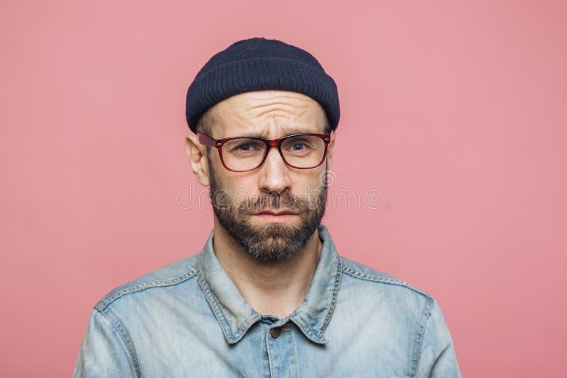 El hombre barbudo gruñón con la expresión ofendida, siendo descontentado con algo, cara de los ceños fruncidos, lleva las gafas,  fotos de archivo