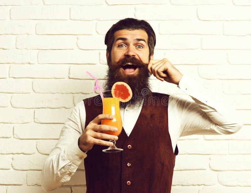 El hombre barbudo hermoso con la barba y el bigote largos tiene pelo elegante en la cara feliz que sostiene el vidrio de la bebid imagen de archivo libre de regalías