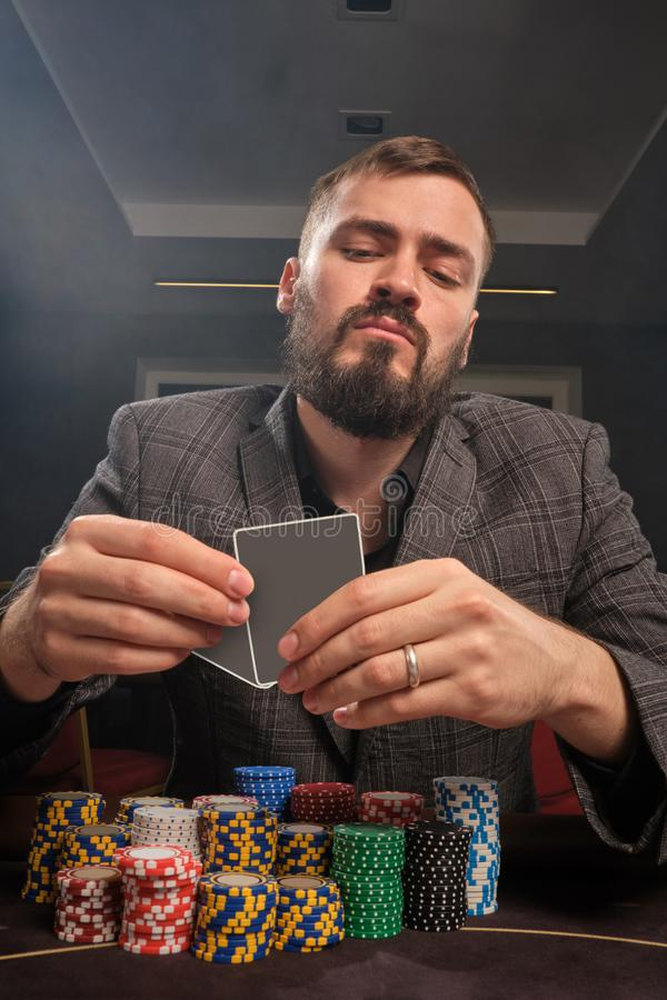 El hombre barbudo hermoso está jugando el póker que se sienta en la tabla en casino imagenes de archivo