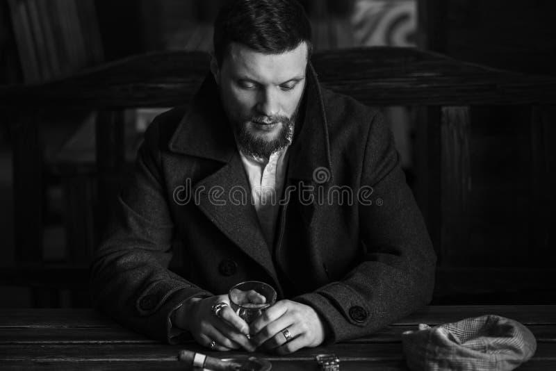 El hombre barbudo joven bebe el whisky en un pub, estilo del vintage fotografía de archivo