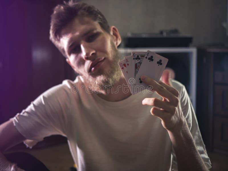 El hombre barbudo joven en tarjetas casuales del playng que se sostienen muestra el retrato de algunos trucos en casa fotos de archivo