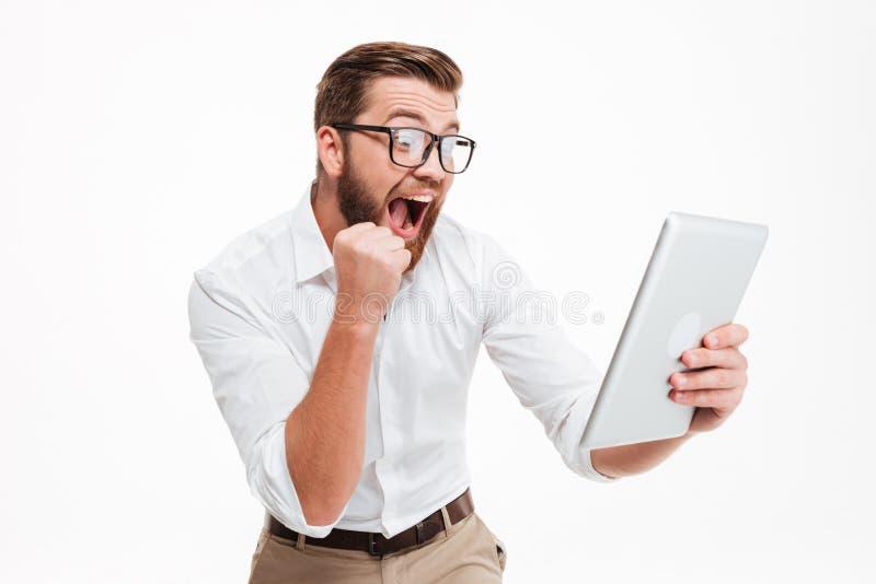El hombre barbudo joven feliz que usa la tableta hace gesto del ganador imágenes de archivo libres de regalías