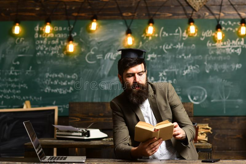 El hombre barbudo leyó el libro en sala de clase Inconformista del científico con el libro en la pizarra Hombre de negocios en el imagen de archivo libre de regalías