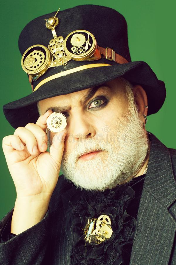 El hombre barbudo mira a trav?s de la rueda dentada fotos de archivo