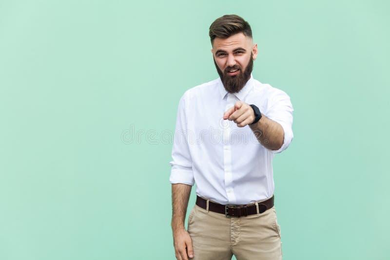 El hombre barbudo que señala el finger en la cámara y la mofa sobre alguien fotos de archivo