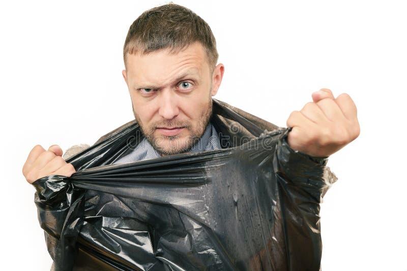 El hombre barbudo rompe la bolsa de plástico en el fondo blanco fotos de archivo