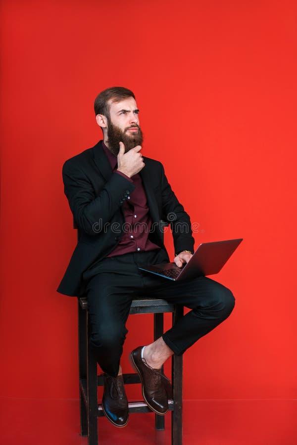 El hombre barbudo se sienta en silla con el ordenador portátil fotos de archivo
