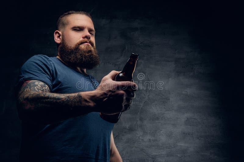 El hombre barbudo sostiene la botella de cerveza fotografía de archivo libre de regalías