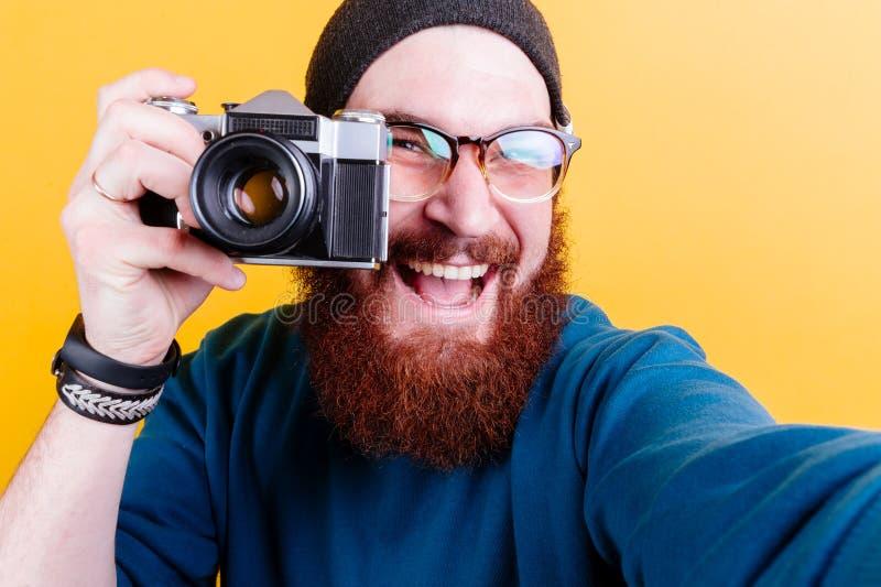 El hombre barbudo sostiene una cámara de la película del vintage imagen de archivo libre de regalías