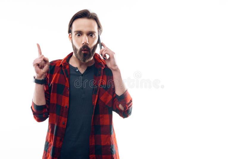 El hombre barbudo tiene idea mientras que habla en el teléfono fotos de archivo