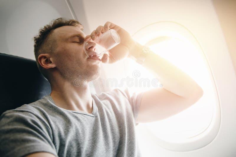 El hombre bebe el agua en un aeroplano antes de despegue El concepto pone los oídos foto de archivo