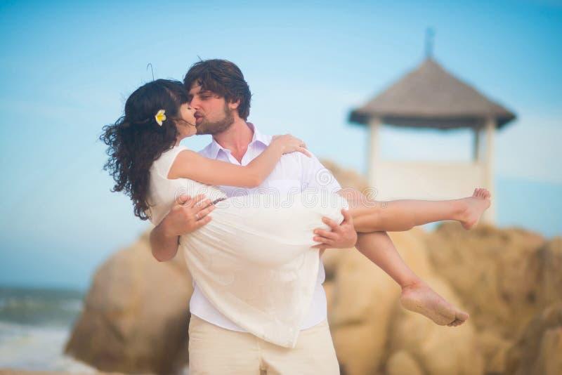 El hombre besa a una mujer hermosa, deteniéndola en sus brazos, contra las rocas, el mar y el cielo fotografía de archivo libre de regalías