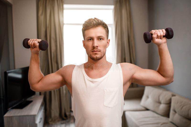 El hombre bien hecho joven entra para los deportes en el apartamento Él hace la prensa del hombro usando pesas de gimnasia Mirada imagen de archivo libre de regalías