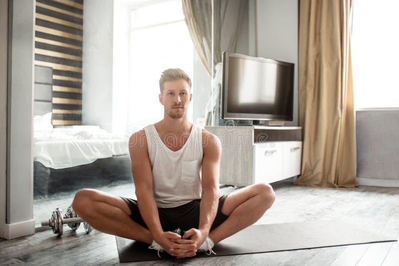 El hombre bien hecho joven entra para los deportes en el apartamento Manos tranquilas y pacíficas del control del individuo en pi foto de archivo