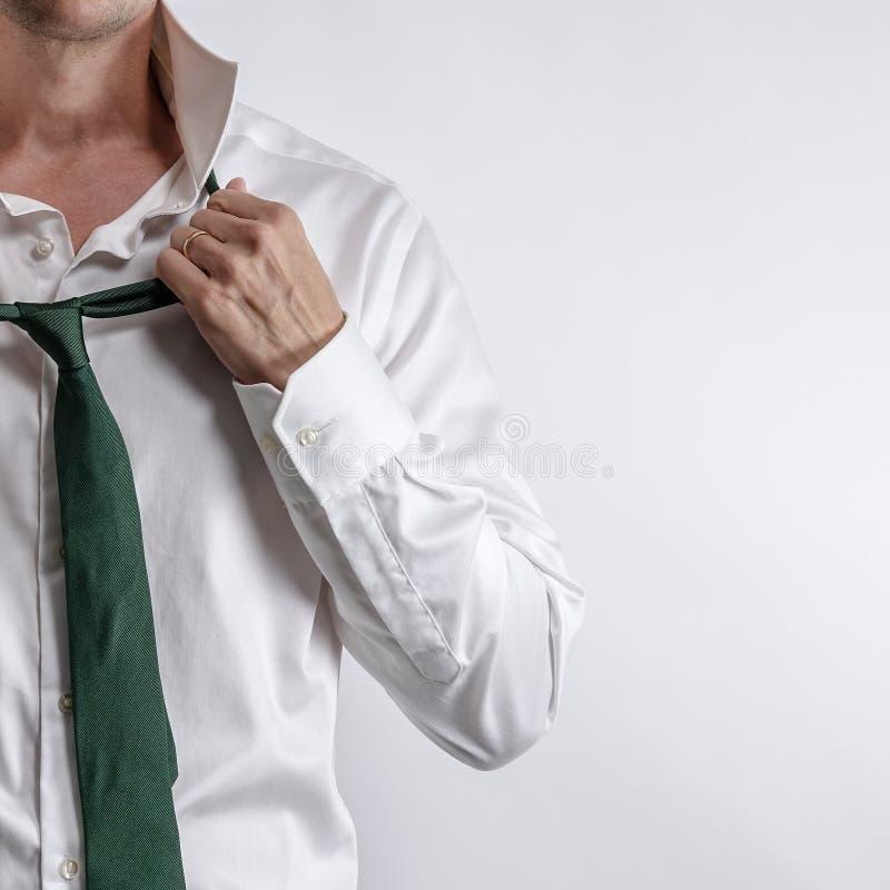 El hombre bien vestido en la camisa blanca consigue vestido/desnudó imagen de archivo