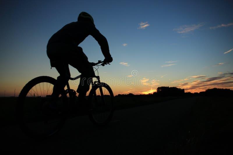 El hombre biking en la puesta del sol foto de archivo libre de regalías
