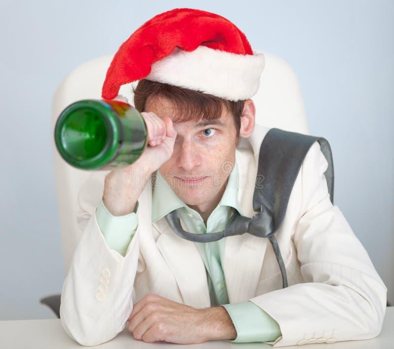 El hombre borracho en casquillo de la Navidad juega con la botella foto de archivo libre de regalías