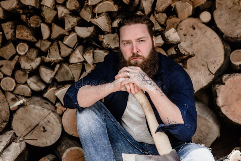El hombre brutal con una barba vestida en ropa casual con los tatuajes en sus manos sostiene el hacha que se sienta cerca de la m fotos de archivo libres de regalías