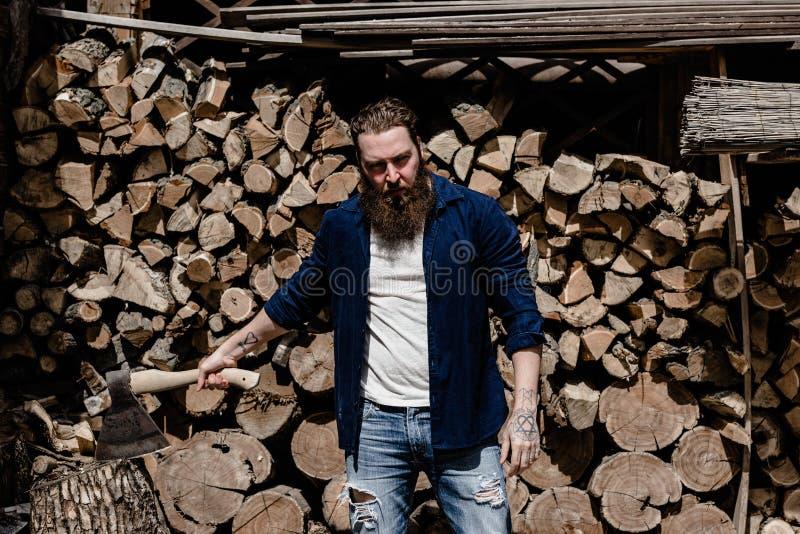 El hombre brutal con una barba vestida en ropa casual con los tatuajes en sus manos sostiene el hacha que se sienta cerca de la m foto de archivo libre de regalías