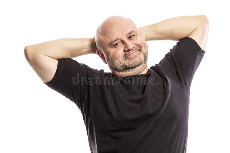 El hombre calvo adulto con las manos detrás de su cabeza está sonriendo Aislado en un fondo blanco imágenes de archivo libres de regalías