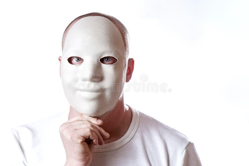 El hombre calvo cubre su cara con la máscara en el fondo blanco fotos de archivo libres de regalías