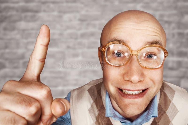 El hombre calvo del retrato con los vidrios en un fondo blanco de la pared de ladrillo muestra un dedo índice para arriba y sonri imagenes de archivo