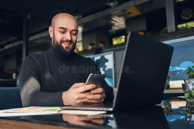 El hombre calvo est? trabajando en el ordenador port?til y el smartphone de las aplicaciones mientras que se sienta en caf? en la fotografía de archivo libre de regalías