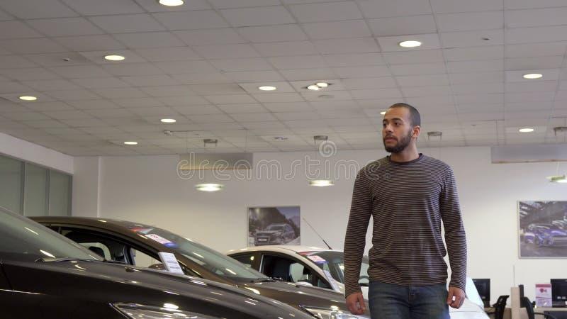 El hombre camina a lo largo de la sala de exposición del coche foto de archivo libre de regalías