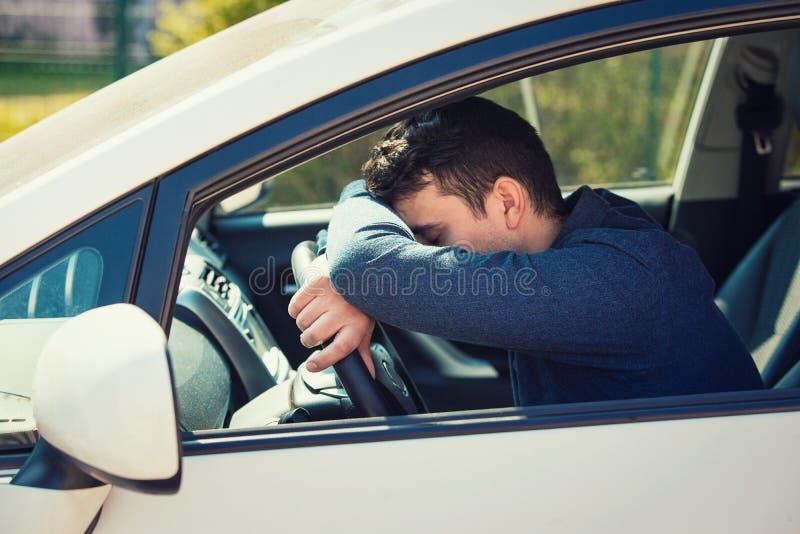 El hombre casual casi durmiente mantiene la mano y la cabeza en el volante que es el esperar cansado el atasco después de trabajo imagenes de archivo