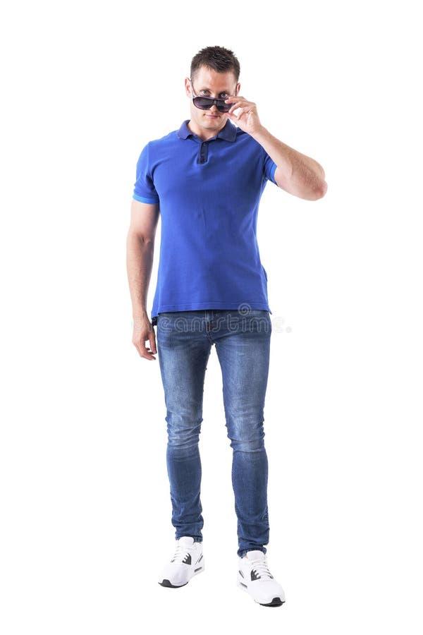El hombre casual joven confiado serio que sostiene las gafas de sol con sobre los vidrios mira la cámara fotos de archivo libres de regalías