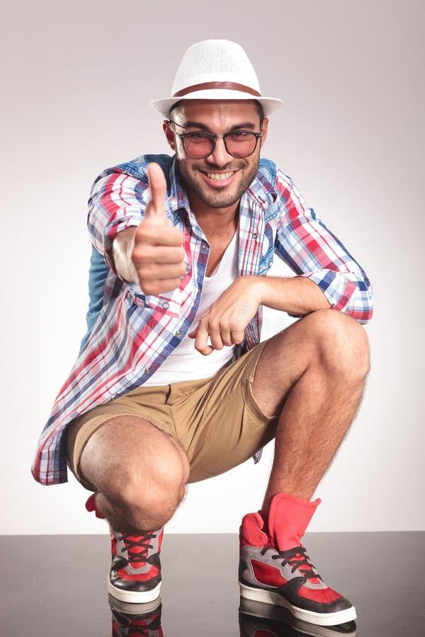 El hombre casual joven feliz que muestra los pulgares sube gesto fotos de archivo