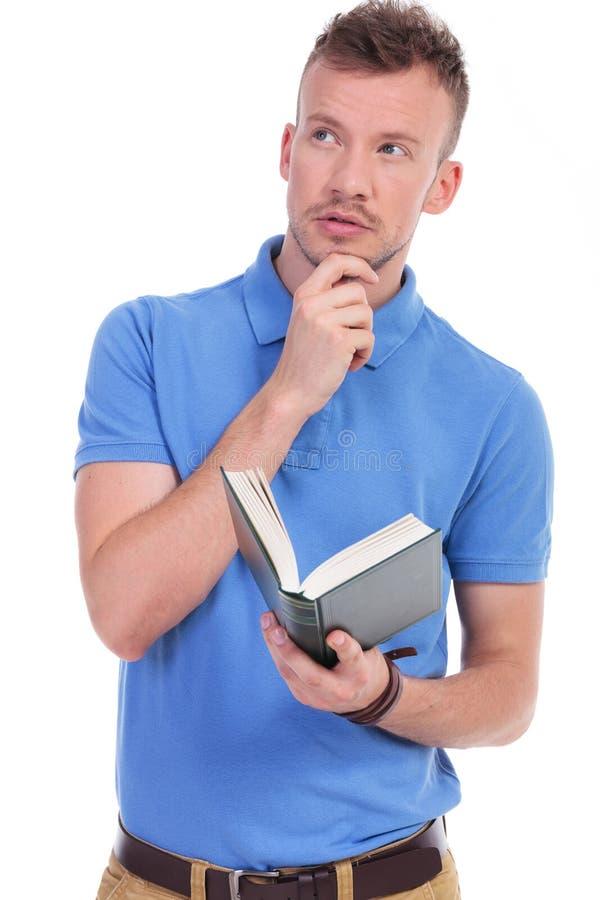 El hombre casual joven pensativo sostiene el libro fotografía de archivo libre de regalías