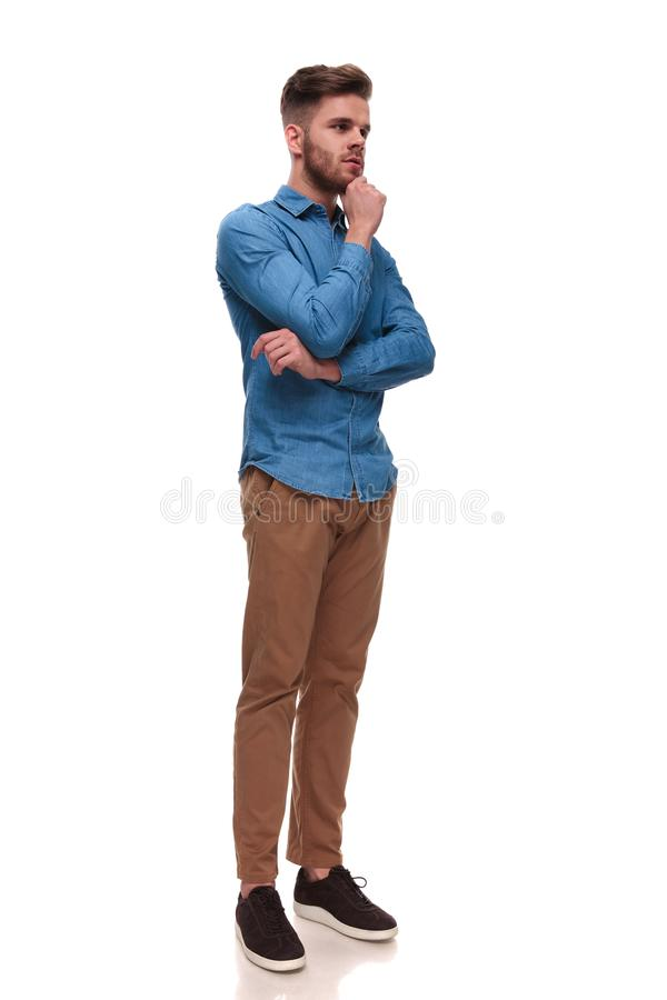 El hombre casual pensativo con la barba mira para echar a un lado mientras que se coloca imagenes de archivo