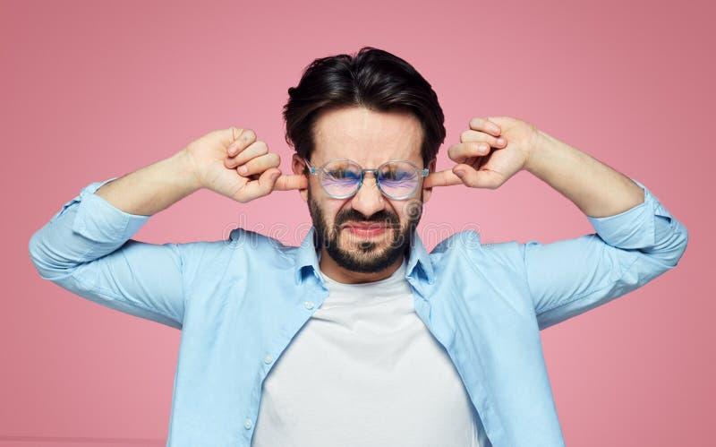 El hombre caucásico agotador enojado evita sonidos ruidosos en la calle, tapa los oídos y mantiene ojos cerrados, aislado en fond fotografía de archivo libre de regalías