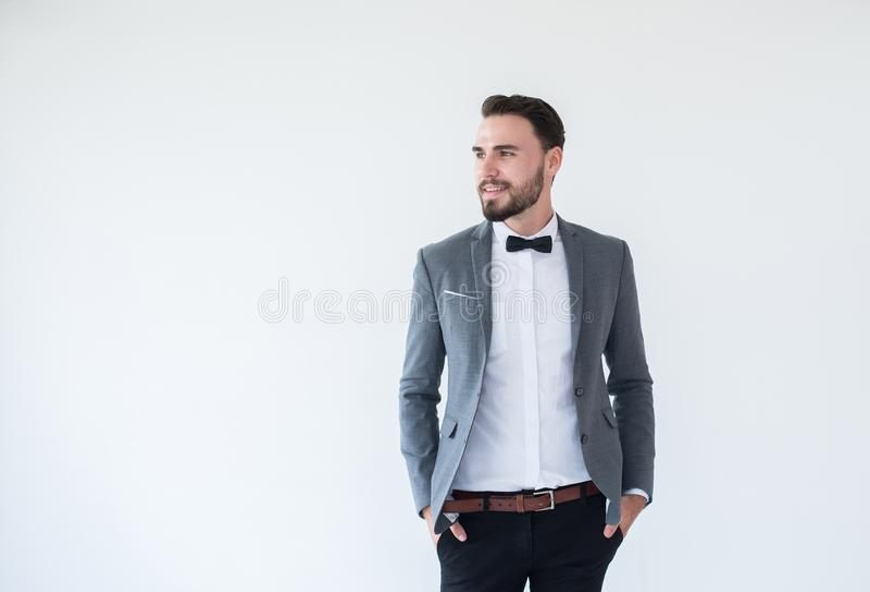 El hombre caucásico hermoso con barbudo en la situación formal del smoking y del traje y la sonrisa en el fondo blanco, copia el  imagenes de archivo