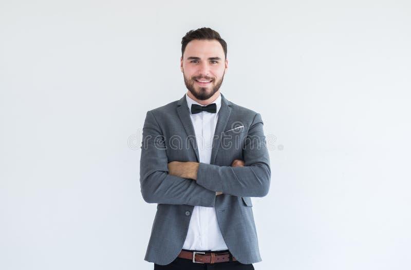 El hombre caucásico hermoso con la barba en la situación formal del smoking y del traje y los brazos cruzados en el fondo blanco, imagen de archivo libre de regalías