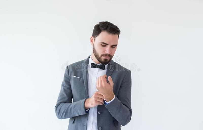 El hombre caucásico hermoso con la barba en la situación formal del smoking y del traje y vestido para arriba en el fondo blanco, fotos de archivo libres de regalías