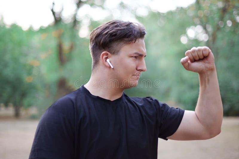 El hombre caucásico hermoso joven se coloca de apretón de su puño para arriba, en el centro de la expresión de Sterne del parque  imagen de archivo libre de regalías