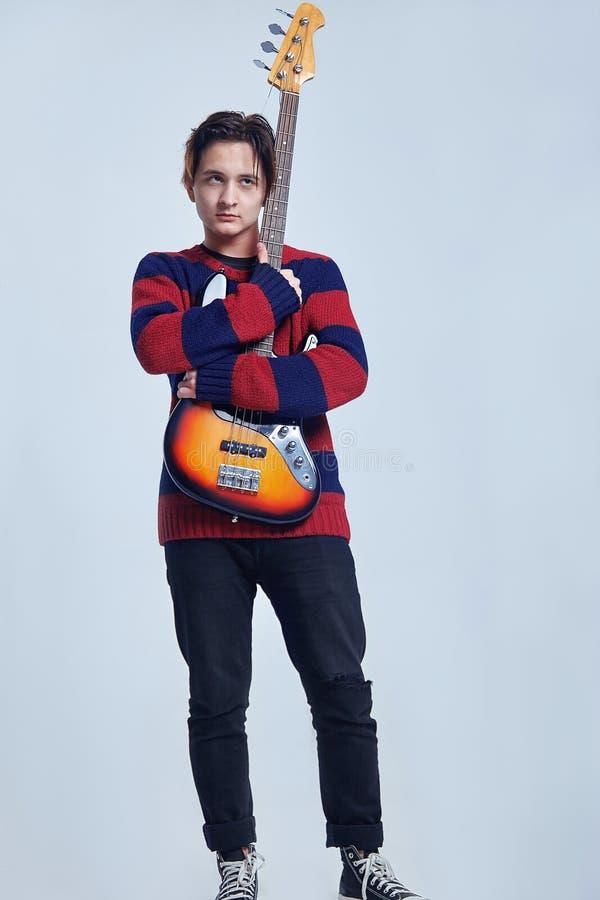 El hombre caucásico hermoso joven se coloca huging la guitarra imagen de archivo libre de regalías